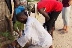 Weiter werden die mitgebrachten Pflanzen verteilt. Banique pflanzt den ersten Baumsetzling im Dorf Patar ein.