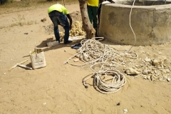 Um den Brunnen auszubauen, brachte der Brunnenbauer folgendes mit: nur eine lange, dünne Schnur, einen abgenutzten kleinen Eimer und einen… um zu graben.