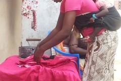 So sieht der Alltag in Dakar aus.  Das Kind auf den Rücken und die Kleidung mit altem Bügeleisen bügeln.