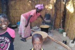 Es ist Essenszeit! Die Mama kocht und die Kinder leisten ihr Gesellschaft.