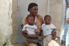 Die Oma hält die beiden Zwillinge für einen besseren Ausblick auf dem Schoß.