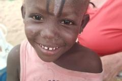 Die Kleine freut sich über die Malkünste der anderen Kinder auf ihrer Stirn. Dafür brauchten sie nur ein Stück Steinkohle aus dem Sand.